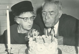 Mrs. Gertrude Miller and John Holmes blowing out candles at Gordon Head Mutual Improvement Societ...