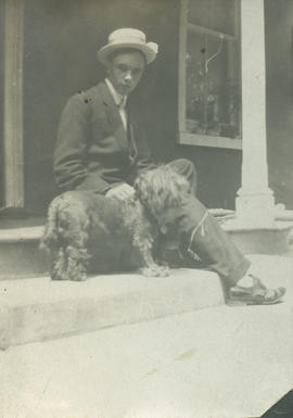 Boy sitting on step with dog