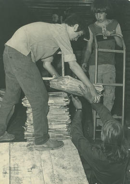 Boys handling newspapers at recycling depot