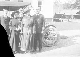 Women and Naval officers beside car