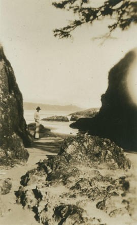 Man standing at rocky shoreline