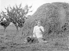 Alice Maude Aitkens and dog in front of hay stack on the Aitkens farm