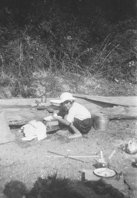 Lorna Grace Aitkens washing camping dishes at Cordova Bay beach