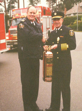 Assistant Fire Chief Ron Stubbings presenting a fire extinguisher to Fire Chief Murray Brydan on ...