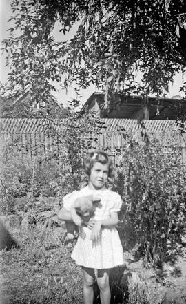 Girl in garden holding teddy bear