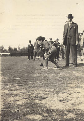 Boy bowling as spectators look on, Burnside Lawn Bowling Club