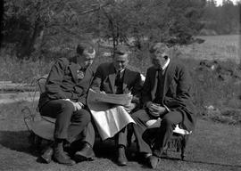 George Edward Andrew in centre, reading Daily Colonist newspaper with two men
