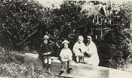 Mrs A.H. Whitehead with her children Ted, Bill and Jack, in a dugout canoe, 1922