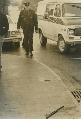 Constable John Jackson walking past Saanich Police van following an accident