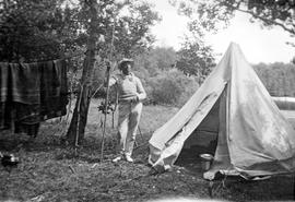 Frank Aitkens with fishing pole, tenting at Max Lake, Manitoba