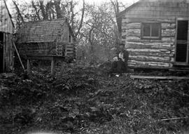 Man and dog in front of log houses
