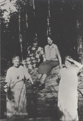 Agnes Cunningham (left) and other family members with fallen log during tree clearing on their Elk Lake property