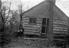 Man and dog in front of log houses, taken on the Prairies