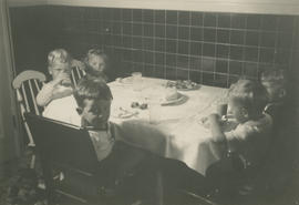 Children sitting around table for birthday party