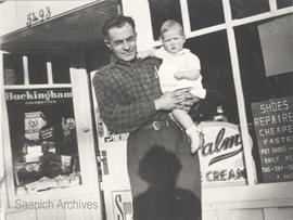 Chuck Cunningham holding a baby in front of his store