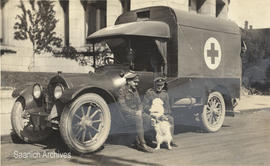 Postcard of Muggins the Red Cross dog with two soldiers and a Red Cross ambulance