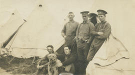 WWI soldiers and dog outside tent