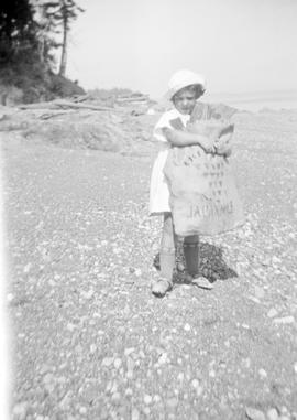 Lorna Grace Aitkens carrying wood for the campfire, Cordova Bay beach